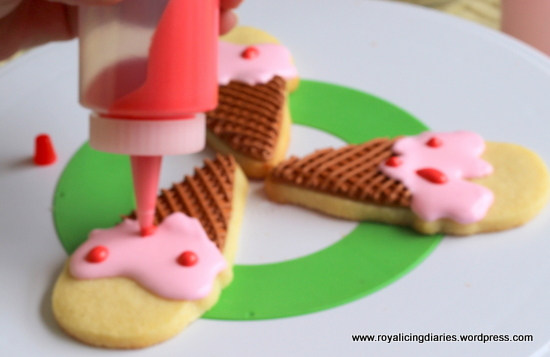 Adding strawberries to the ice cream cone cookies