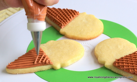 Adding the lines on the ice cream cone cookies