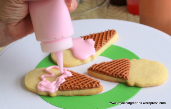 Adding strawberry ice cream to the ice cream cones